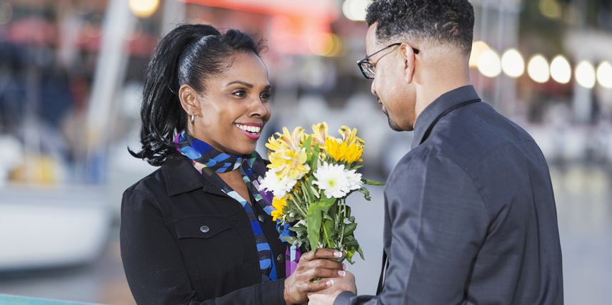 man-giving-flowers-to-young-latino-woman