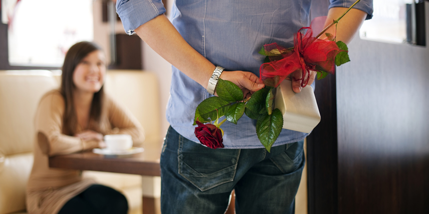 man-hiding-gift-and-flowers-for-woman
